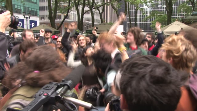 young protesters jump around and chant to the sound of drums at the may day occupy wall street rally in bryant park nyc - bryant park stock videos and b-roll footage