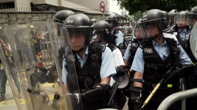 vídeos de stock, filmes e b-roll de young protesters moving railings as riot police stand their ground at protests over extradition bill in centre of hong kong - legislação