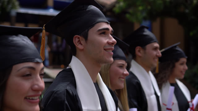 young proud male student graduating and then looking at camera smiling - graduation gown stock videos and b-roll footage