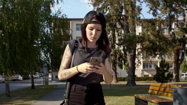 giovani punk donna utilizzando un cellulare - piercing video stock e b–roll