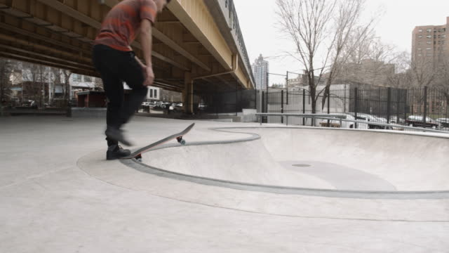 A young, racially ambiguous, real person skates a pool in a Brooklyn, NYC skatepark - 4k