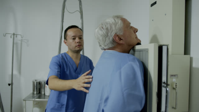 young radiologist getting ready a senior patient for a lung xray - x ray image stock videos & royalty-free footage