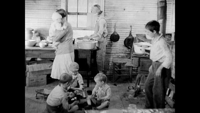 / young raggedy boy playing with empty tin cans / woman cooks dinner with a baby on her hip / farmhouse kitchen with mother and six children / family...