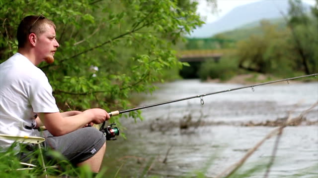 Young readhead man angling in admirable enviroment