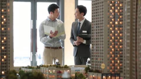stockvideo's en b-roll-footage met young realtor showing architectural model to customer,hd - klanten georiënteerd