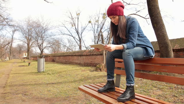 Young rebel woman in park using a digital tablet.