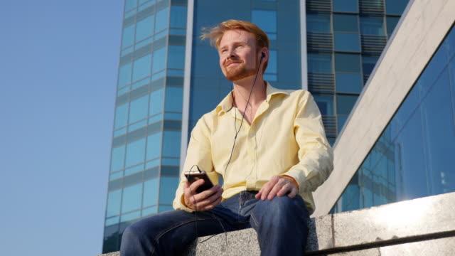 Eine junge rothaarige Kerl Kopfhörer anhören von Musik in der Stadt
