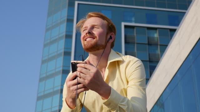eine junge rothaarige kerl kopfhörer anhören von musik in der stadt - 20 24 years stock-videos und b-roll-filmmaterial