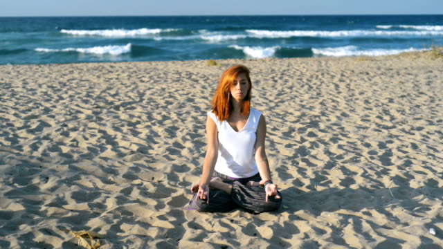 Young redhead woman at early 30s meditating on the beach I