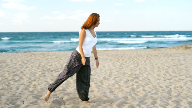 Young redhead woman at early 30s meditating on the beach IV