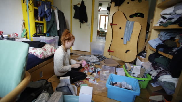 vidéos et rushes de young redhead woman cleaning room and organizing into bins - messy bedroom