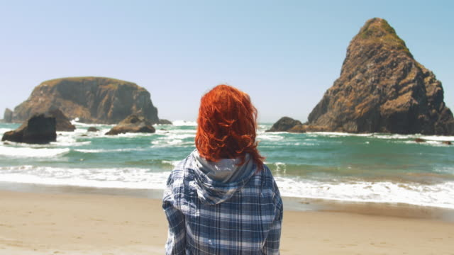 stockvideo's en b-roll-footage met young redhead woman gazing out at idyllic beach landscape - oregon amerikaanse staat