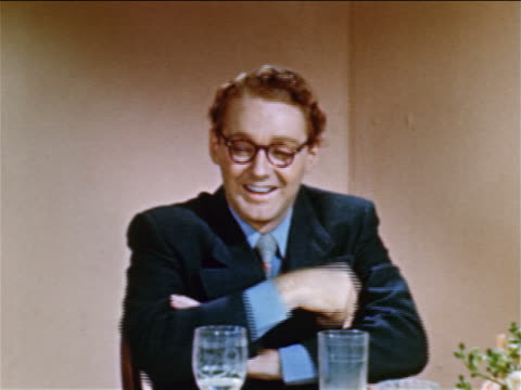 vídeos y material grabado en eventos de stock de 1952 young redheaded man with glasses sitting at table talking to someone offscreen / industrial - 1952