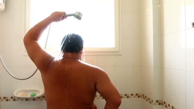 vidéos et rushes de détendue jeune homme prenant une douche - prendre un bain