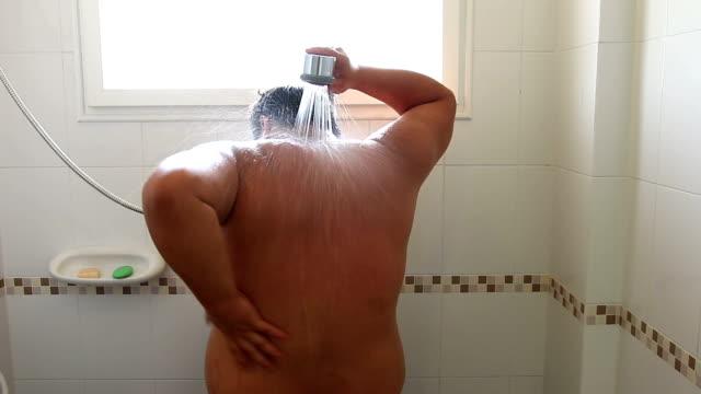 vidéos et rushes de détendue jeune homme prenant une douche - laver
