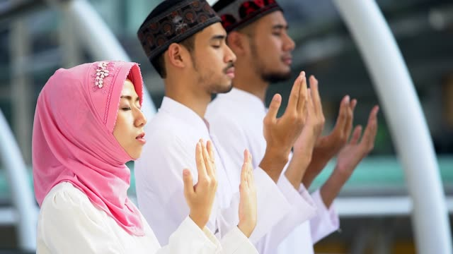 young religious muslim men and women praying together inside the mosque. - islam stock videos & royalty-free footage