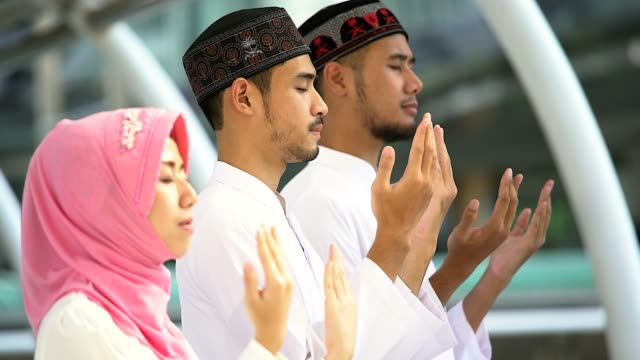 young religious muslim men and women praying together inside the mosque. - koran stock videos and b-roll footage