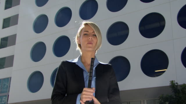 MS LA Young reporter talking microphone in front of modern office building / Miami, Florida, USA