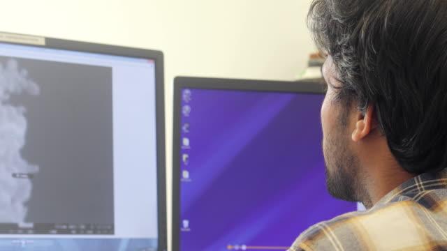 junge forscher analysieren wissenschaftliche probe auf computer-monitor - über die schulter stock-videos und b-roll-filmmaterial