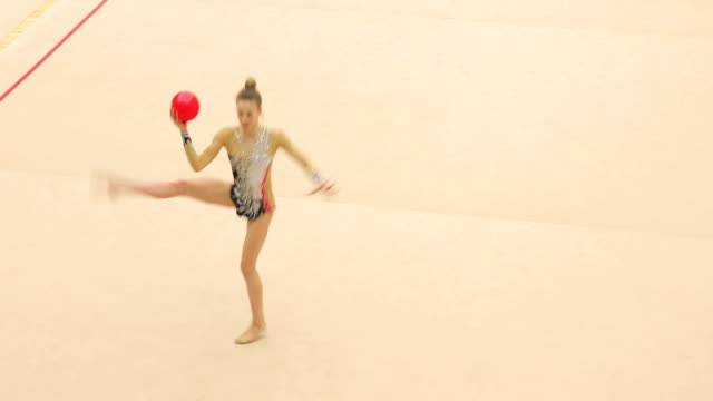 young rhythmic gymnastics athlete performing - persona di sesso femminile video stock e b–roll
