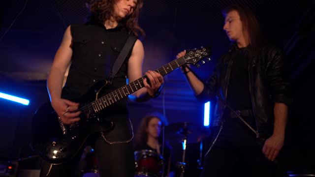 stockvideo's en b-roll-footage met jonge rotsband die hun nieuw lied in muziekstudio speelt - zanger