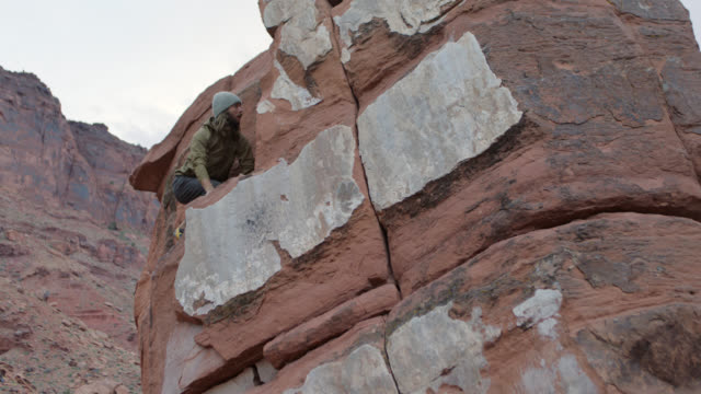 young rock climber carefully scales tall sandstone formation in moab. - outcrop stock videos and b-roll footage