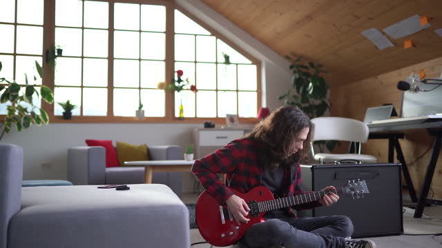 young rock musician sitting on floor and playing guitar at home - rock musician stock videos & royalty-free footage