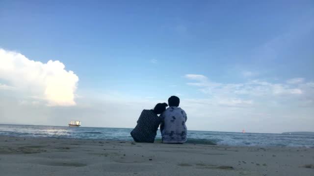 stockvideo's en b-roll-footage met jong romantische koppel is genieten van prachtig uitzicht zittend op het strand - schiereiland baja california