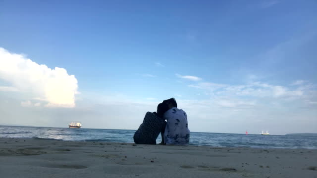 Young romantic couple is enjoying beautiful view sitting on the beach