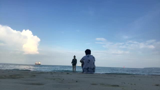 young romantic couple is enjoying beautiful view sitting on the beach - baja california peninsula stock videos & royalty-free footage