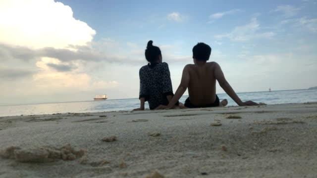ロマンチックなカップルは、ビーチに座って美しい景色を楽しんでいます。
