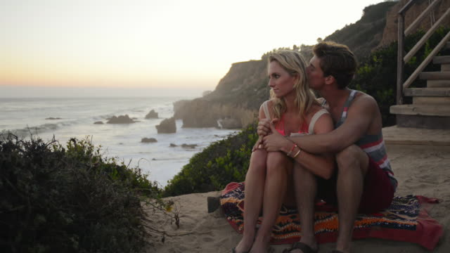 WS Young romantic couple on cliff watching beach sunset together and smilling / Malibu, California, United States