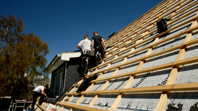 vidéos et rushes de young roofers at work on a roof of a newly built house - couvreur