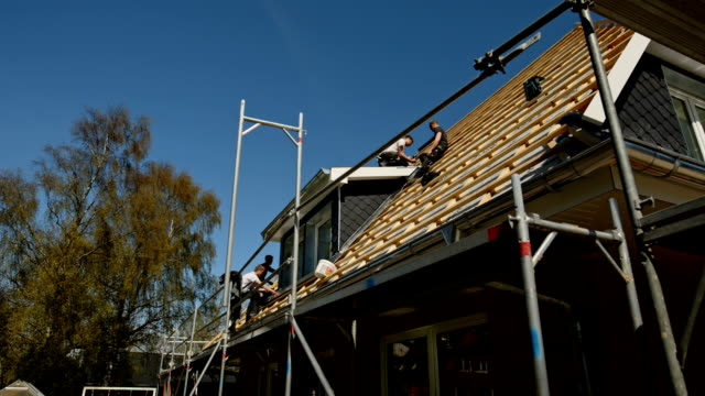 young roofers at work on a roof of a newly built house - scaffolding stock videos & royalty-free footage