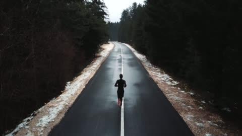 junge läufer auf dem weg zum berg, drohne schuss eines läufers von oben ausgeführt. junge sportler auf ruhigen herbst einsamen pass. filmische drohne wieder anzeigen - männer stock-videos und b-roll-filmmaterial