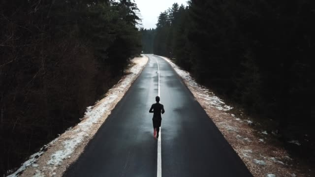 Young runner running on the road to mountain, drone shot of a runner from above.Young athlete on quiet autumn deserted pass. Cinematic drone back view
