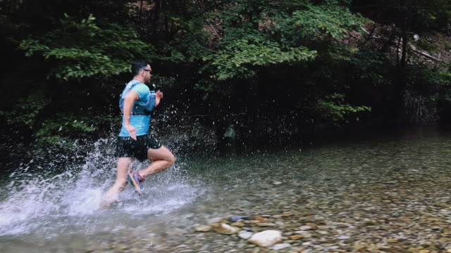 young running through mountain river - triatleta video stock e b–roll
