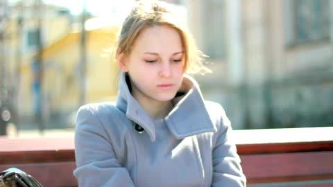 vídeos y material grabado en eventos de stock de mujer triste joven sentado al aire libre únicamente, sensación de estrés - culpabilidad