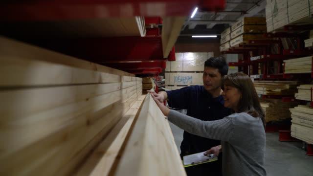 stockvideo's en b-roll-footage met jonge verkoper die verschillende houten materialen aan vrouwelijke klant toont - doe het zelven