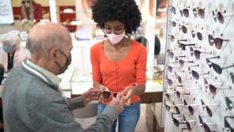 stockvideo's en b-roll-footage met jonge verkoopster die een hogere klant bijstaat die oogglazen in een optische opslag koopt, allebei dragend gezichtsmasker - bril brillen en lenzen