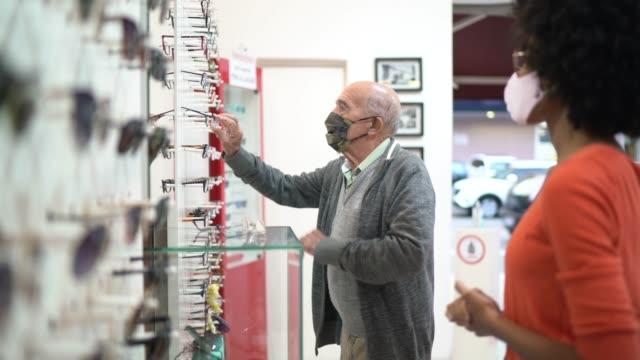 giovane commessa che assiste un cliente senior che acquista occhiali in un negozio ottico, entrambi indossando la maschera facciale - lente strumento ottico video stock e b–roll