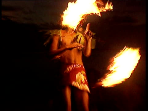 young samoan man wearing traditional dress juggles with fire on beach at night as other sit and watch zoom into man spinning fire baton around head savaii samoa - dress stock videos and b-roll footage