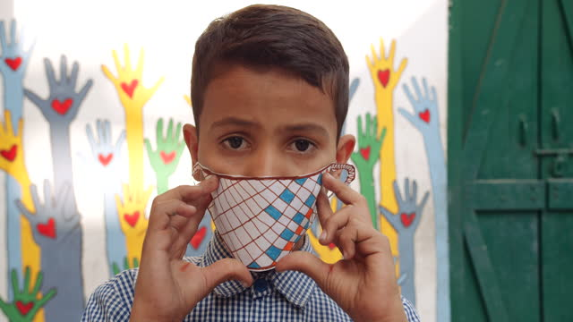young school boy displays a paper sketched and cut drawing rough of a face mask for coronavirus pandemic covid-19 for protection also from air pollution for new normal as he holds it in front of his face and shows to camera pov personal perspective - pencil icon stock videos & royalty-free footage