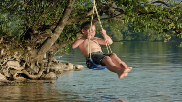 young school boy enjoys himself and his summer holidays while sitting and spinning on a swing mounted on a old tree over water lakesides at the beach of lake staffelsee - digital detox - nur kinder stock-videos und b-roll-filmmaterial