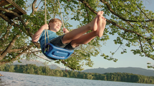 young school boy in jeans shorts and blue shirt sits on a swing mounted on a tree hanging over water lakesides by the beach of lake Staffelsee and is enjoying himself while swinging in the late evening sunlight on a nice summer day
