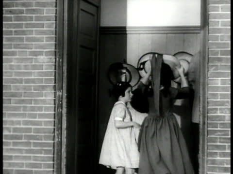 Young school children entering old schoolhouse MS Girls hanging hats on rack INT WS Sitting down in classroom MS Teacher class reciting prayer Turn...