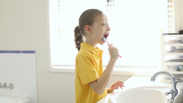 young school girl brushing teeth - back to school stock videos & royalty-free footage