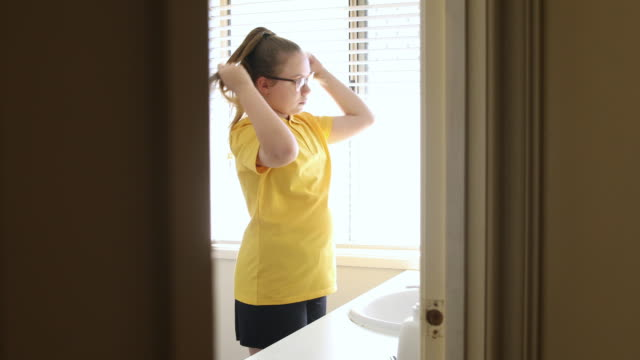 young school girl checking glasses in mirror - school uniform stock videos & royalty-free footage