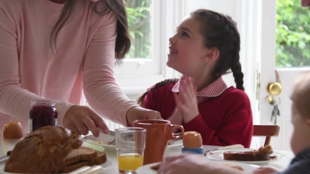 young school girl in uniform having breakfast with family - prima colazione video stock e b–roll