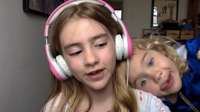 young school girl wearing headphones is distracted by her younger sister during class via video call - two people stock videos & royalty-free footage